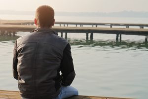 Man sittying on old wooden dock and looking at horizon.